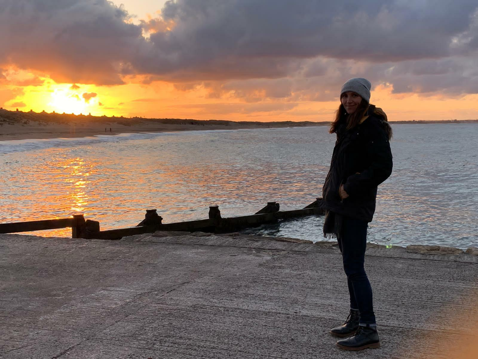 a woman wearing a coat and winter cap at sunset at a boat ramp