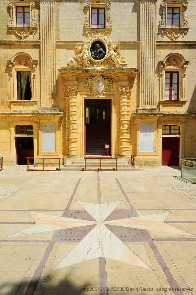 A large Maltese cross is part of the stone tile leading to the entrance to the historical museum at Vilhena Palace, Mdina.