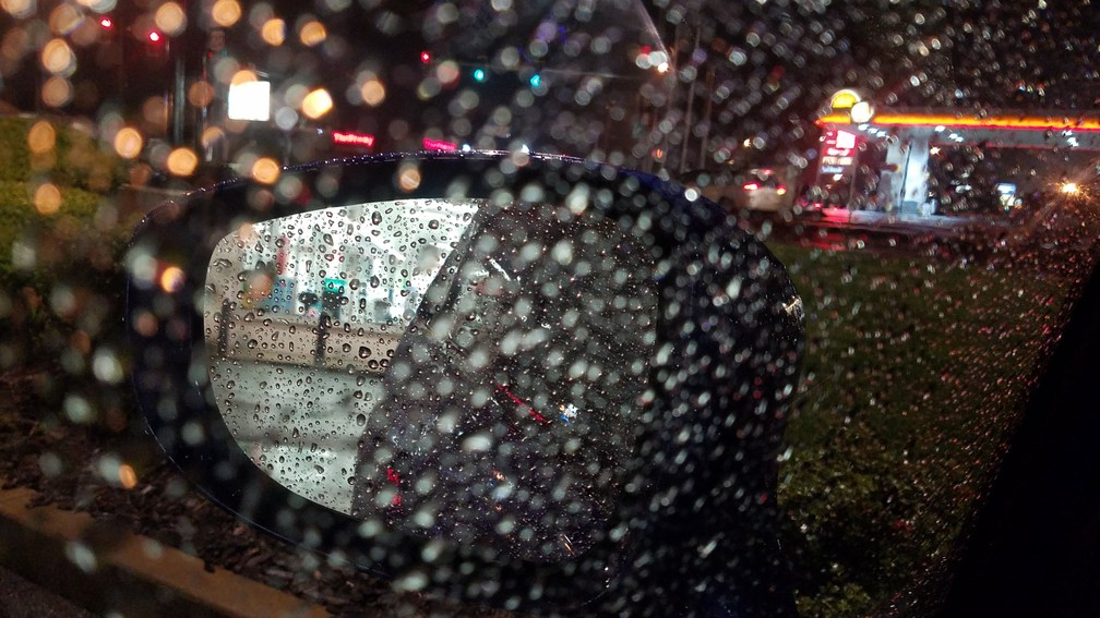rearview mirrors, reflections, rain drops on windshield and night lights from a gas station
