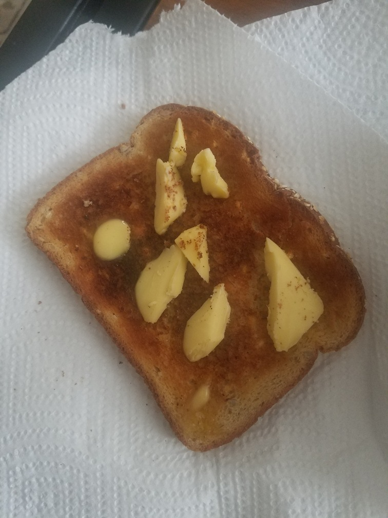a slice of toast with pats of butter on a paper towel