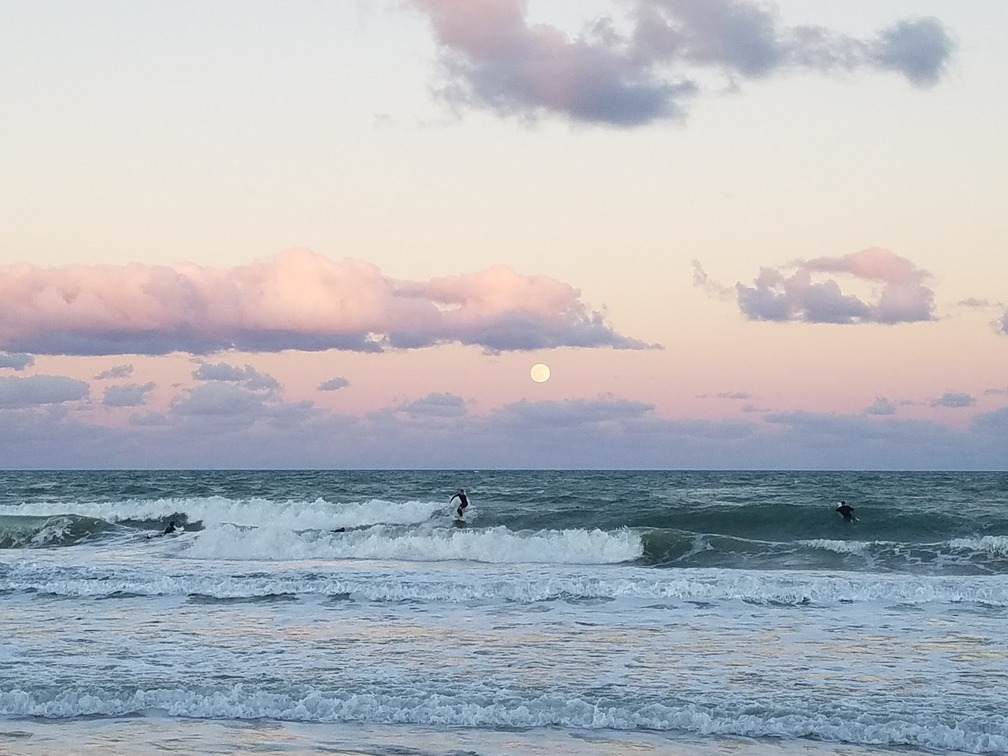 Surfers on the Central Atlantic Coast of Florida surfing under a full moon moonrise.