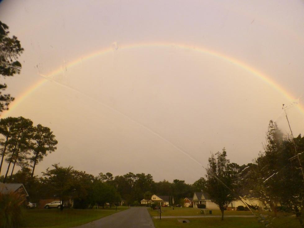 a rainbow over a suburban neighborhood