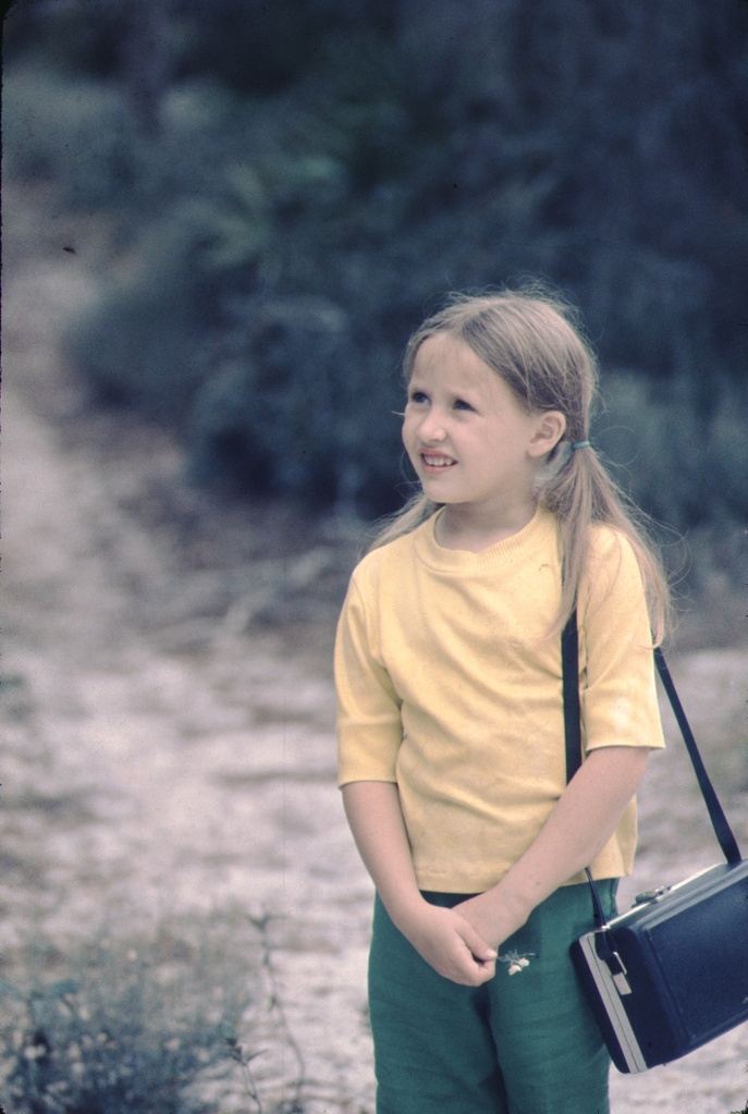 young girl standing on a dirt road