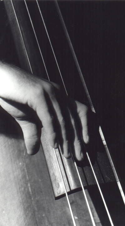 A close up of a hand playing a double bass, monochrome