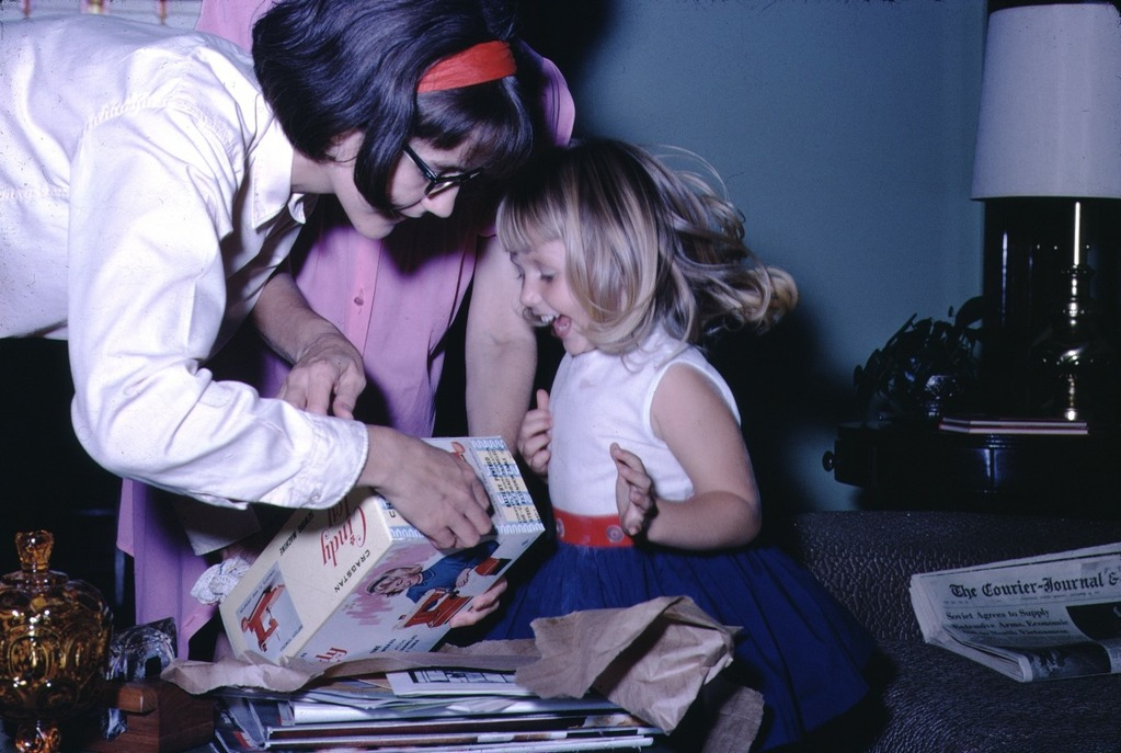 young girl opening a birthday present in 1967. The present is a toy sewing machine called a 'Cindy'