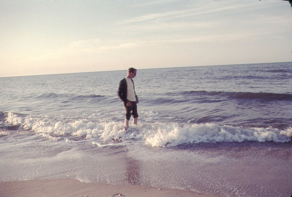 a young man wades in the surf of Gulf of Mexico