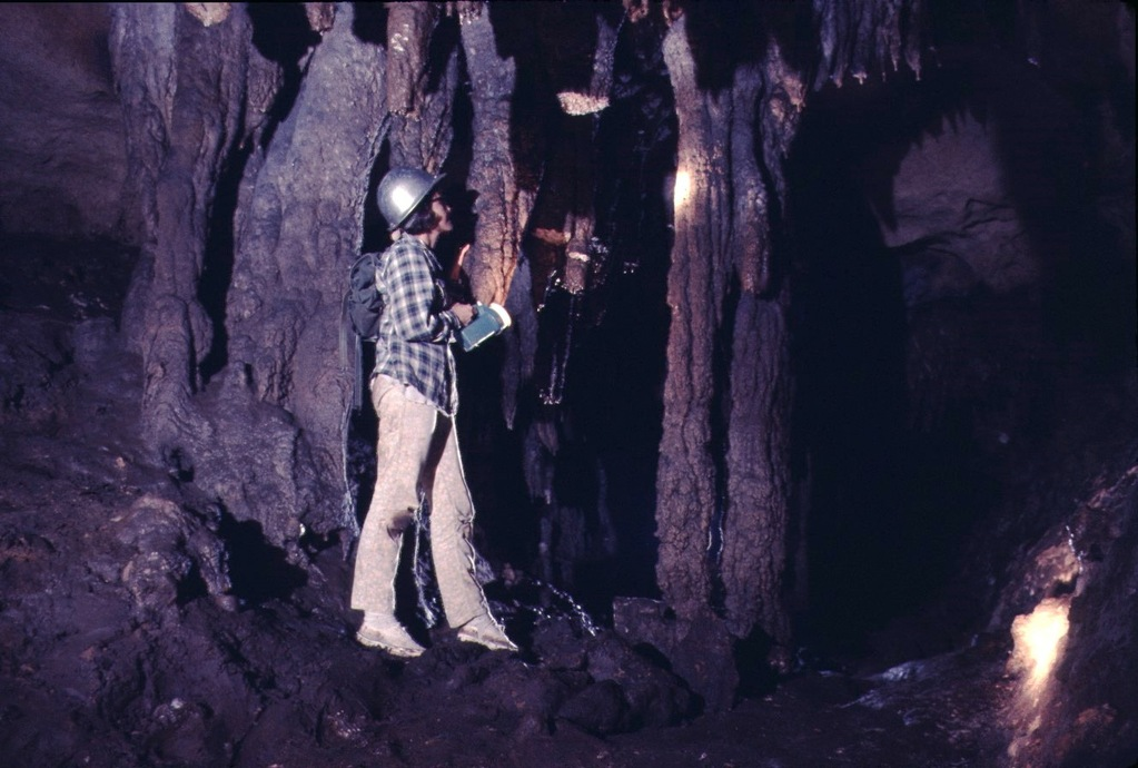 a woman in a hard hat inside a cave