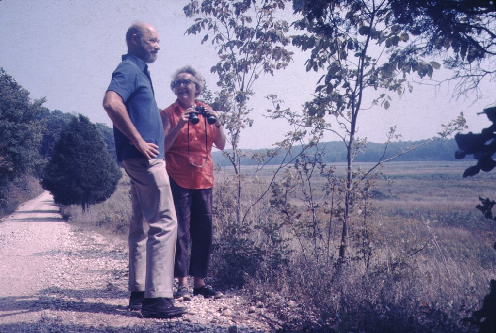 an older couple standing just off a country road looking over a field. The woman is holding binoculars.