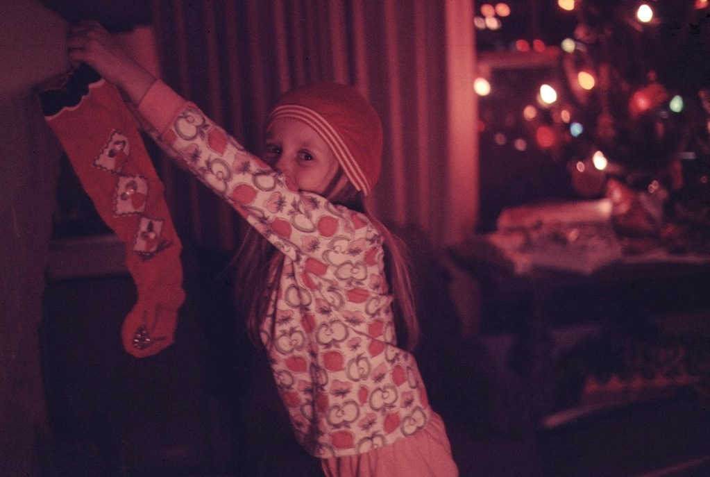 a little girl in a stocking cap hangs a christmas stocking