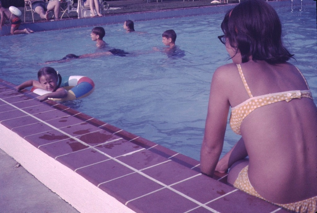mother looks on while her daughter is floating in pool