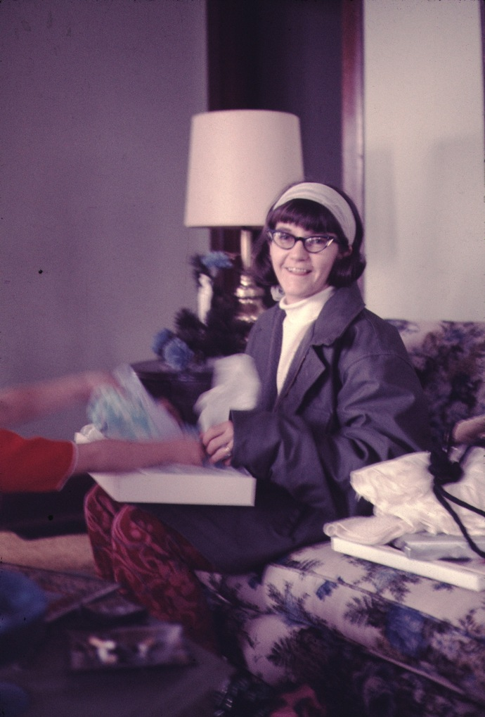 woman opening a present with a lamp behind her