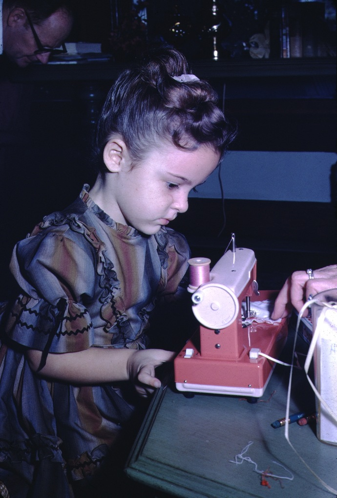 toddler playing with a toy sewing machine