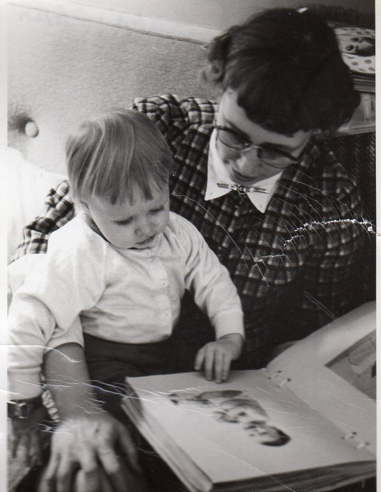 Miss Frances looks at a baby book with Mary Margaret