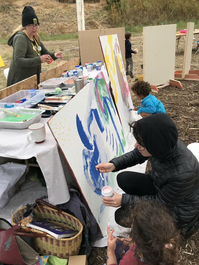 a mother and children painting collaboratively on large boards