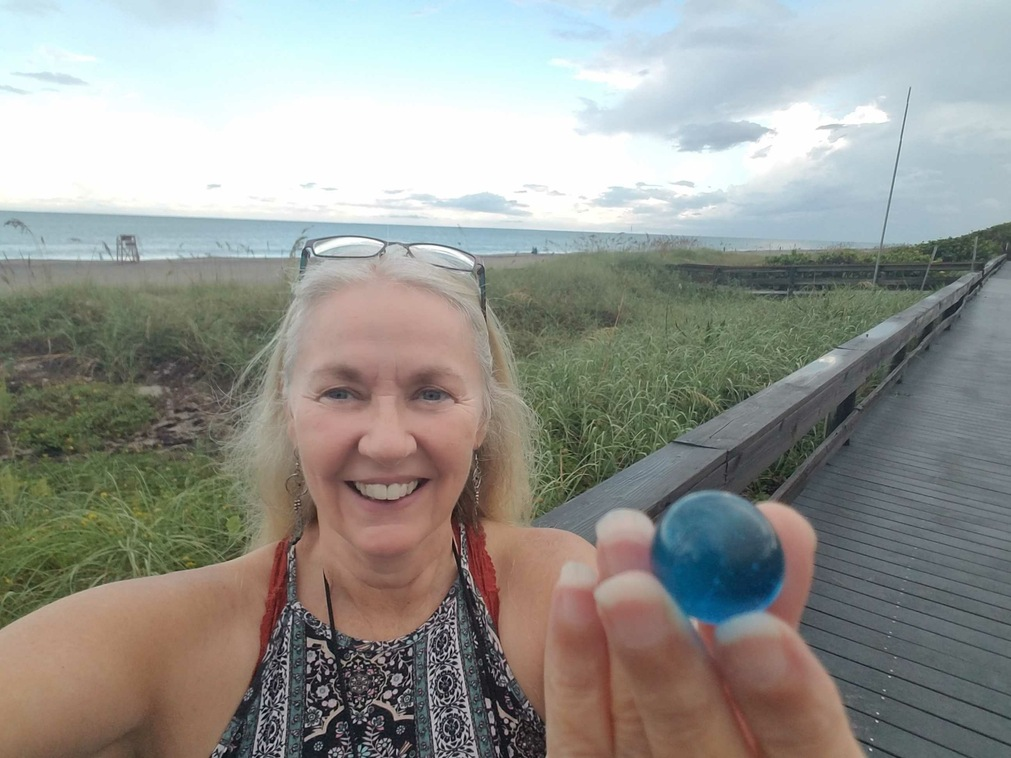 Margaret Warren on the Melbourne Florida Beach boardwalk with a blue marble and with the Atlantic ocean in the background.
