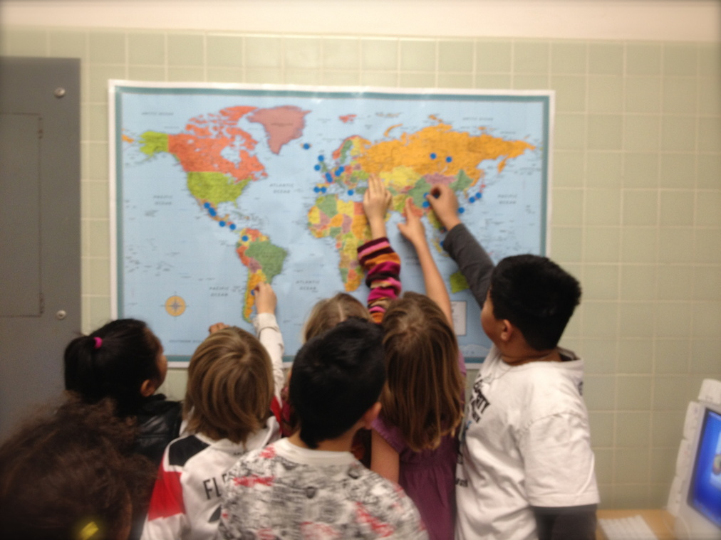 The children point at a map of the world marked with blue sticker dots.