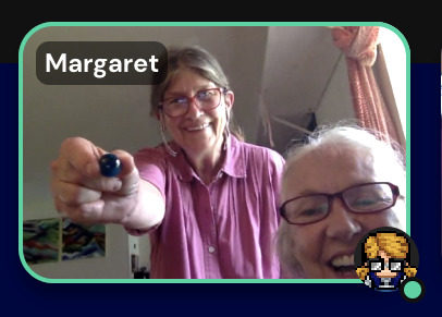 a screenshot of Margaret and Sue. Sue is receiving a blue marble.